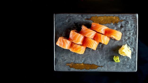 Apetitoso sushi roll de dragão vermelho com salmão, enguia, abacate e caviar tobiko, servido em prato de cerâmica com gengibre e wasabi.