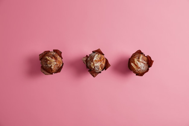 Apetitosos deliciosos muffins em pó com açúcar e saboroso recheio embalado em papel pardo pronto para o consumo. produtos de confeitaria para o seu café da manhã. 3 cupcakes caseiros