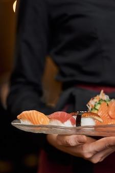 Apetitosos sushi no prato nas mãos dos funcionários do restaurante
