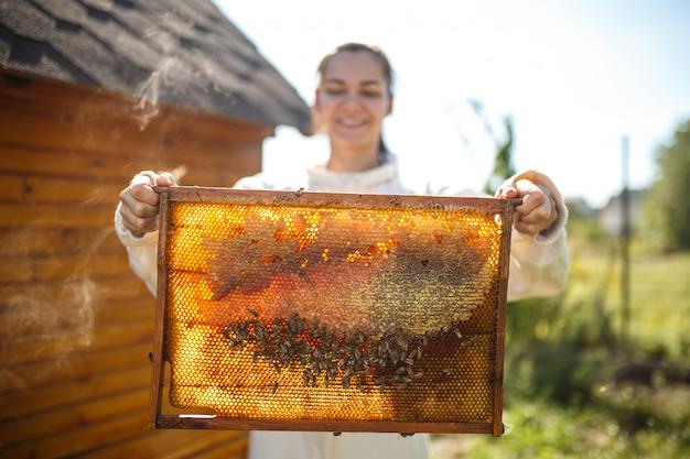 Apicultor feminino jovem segurar a armação de madeira com favo de mel.