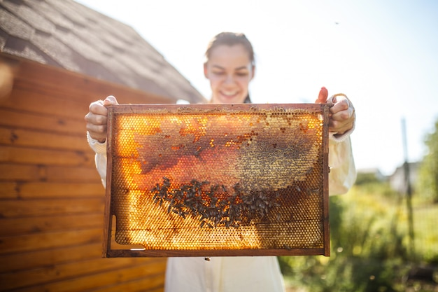 Apicultor feminino jovem segurar a moldura de madeira com favo de mel. colete mel. apicultura.