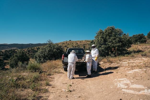 Apicultores que preparam material para coletar mel dos favos de mel