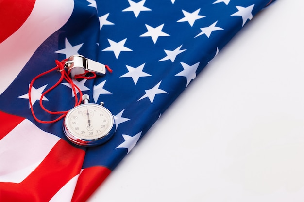 Apito de metal esporte e cronômetro na bandeira americana