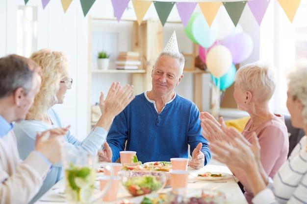 Aplaudindo aniversário homem no jantar