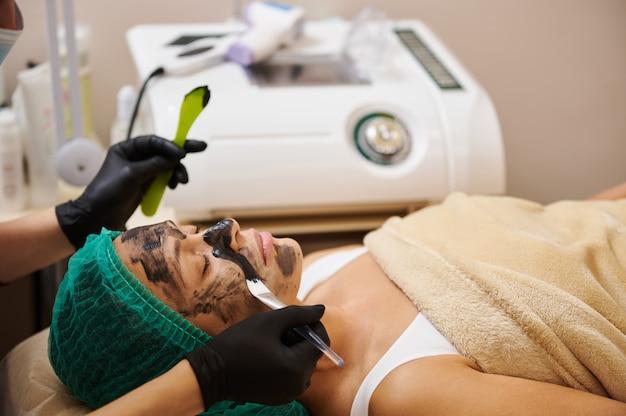 Aplicação da máscara cosmética de carvão vegetal no rosto do paciente com um pincel e espátula