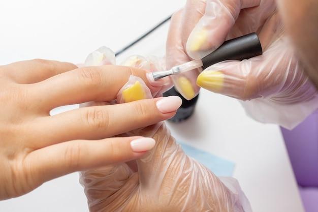 Aplicação de esmalte gel nas unhas. goma-laca. manicure faz manicure no salão. verniz de cor natural. tom nude