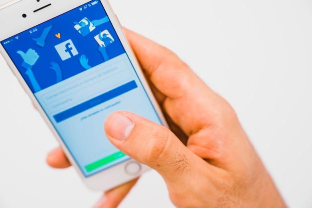 Aplicação de mão, telefone e facebook em primeiro plano