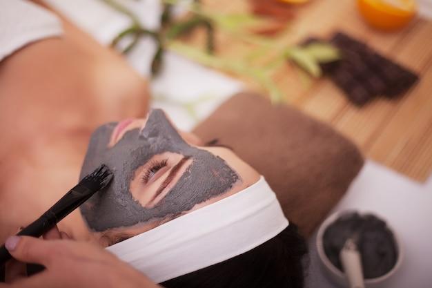 Aplicação de máscara facial no rosto de mulher no salão de beleza