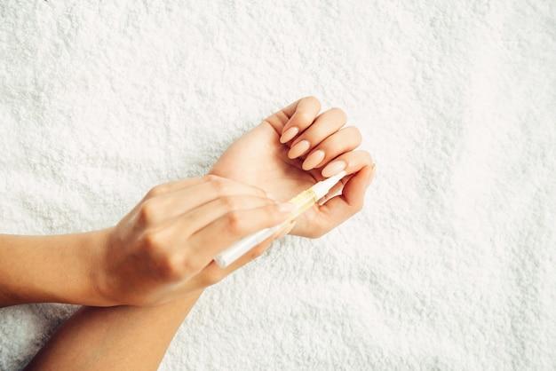 Aplicação de óleo em close-up de cutículas em um fundo branco