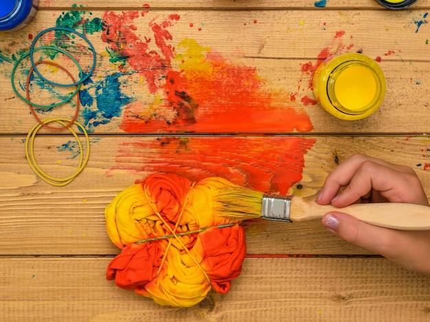 Aplicação de tinta no estilo tie dye nas cores amarelo e verde