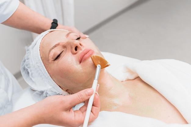 Aplicação de uma escova de máscara de enzima no rosto de uma mulher.