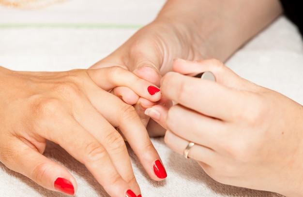 Aplicação de unha polonês nas mãos de uma mulher
