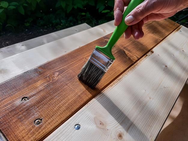 Aplicação de verniz de proteção no piso de madeira de um pátio. pintar madeira do lado de fora.