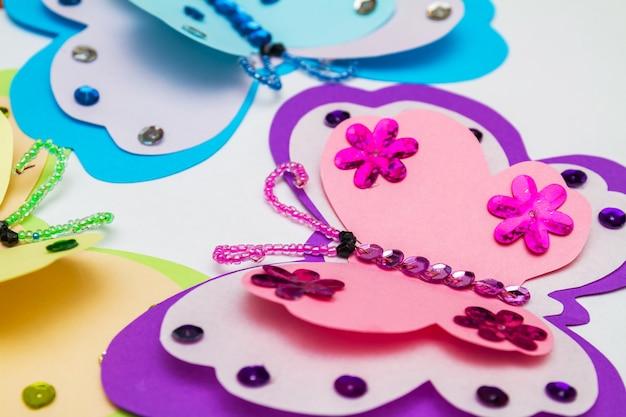 Aplicação feita com pistola de cola quente. três borboletas de papel colorido, lantejoulas multicoloridas, paillettes e miçangas. closeup, foco seletivo