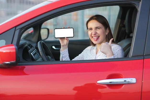 Aplicação móvel para transporte ecológico. carro elétrico de carregamento e olhando para o aplicativo no celular. feche a tela do smartphone. mão segurando o dispositivo inteligente com visor branco.