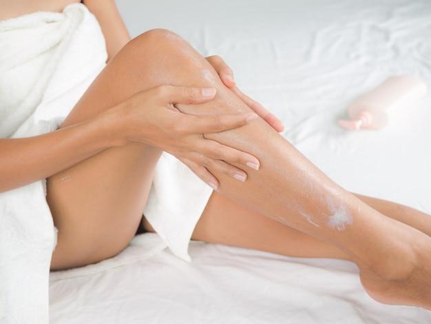 Aplicando o conceito de creme hidratante. corpo de mulher asiática magro, pele bronzeada, cabelo autêntico e preto.
