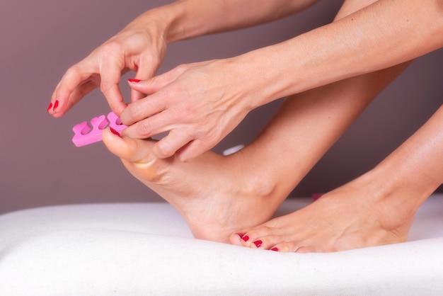 Aplicando pedicure para os pés da mulher com unhas vermelhas, em separadores de dedo do pé-de-rosa.
