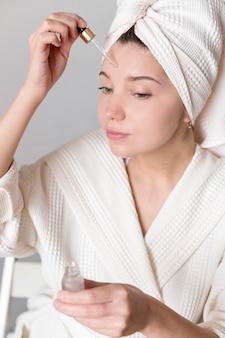 Aplicando soro de rosto feminino
