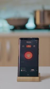 Aplicativo de casa inteligente no telefone colocado na mesa da cozinha em uma casa vazia
