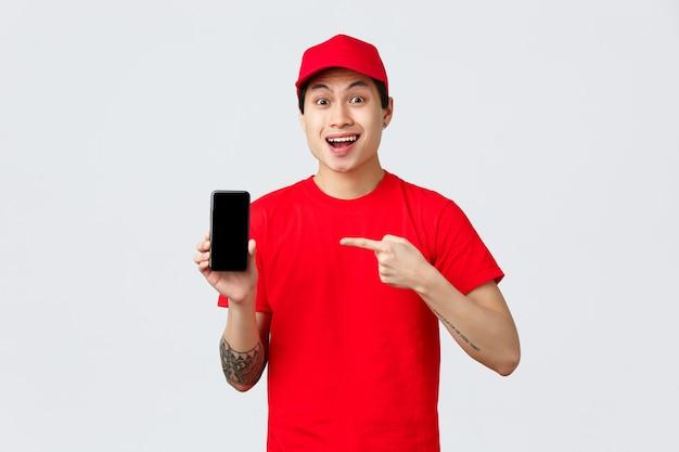 Aplicativo de entrega, compras online e conceito de envio. correio asiático surpreso com boné e camiseta vermelhos, apontando o dedo para o aplicativo do celular, mostrando a tela do smartphone com uma cara divertida