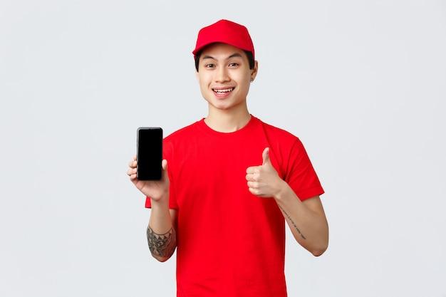 Aplicativo de entrega, compras online e conceito de envio. linda mensageira asiática com camiseta e boné vermelhos, mostre o polegar para cima em aprovação e o aplicativo da tela do celular, forneça um serviço rápido e de qualidade