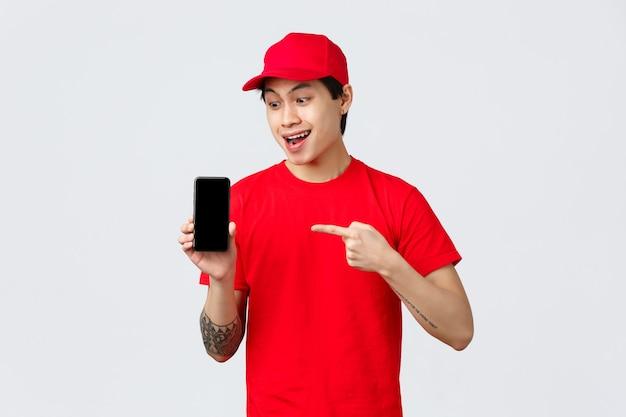 Aplicativo de entrega, compras online e conceito de envio. o mensageiro asiático com camiseta e boné vermelhos recomenda o download do aplicativo para pedidos de comida, quarentena automática, apontando para a tela do smartphone.