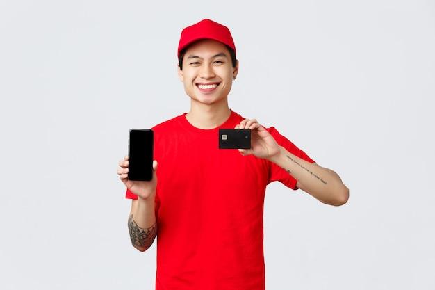 Aplicativo de entrega, compras online e conceito de envio. o mensageiro asiático sorridente e amigável com boné e camiseta vermelha recomenda app, mostre smartphone e cartão de crédito