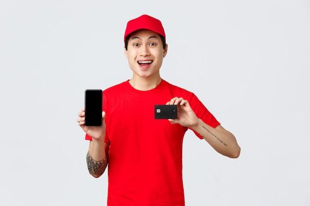 Aplicativo de entrega, pedidos online e conceito de envio. a quarentena não para de fazer compras. correio asiático alegre de boné e camiseta vermelhos, mostrando a tela do smartphone e o cartão de crédito