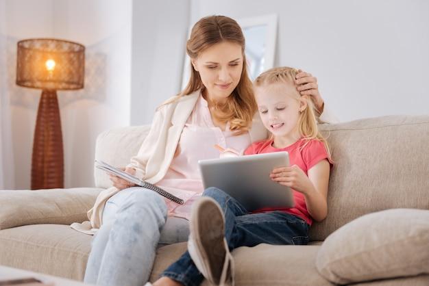 Aplicativo em desenvolvimento. boa garota inteligente e positiva sentada junto com a mãe e usando um tablet enquanto joga um jogo de desenvolvimento