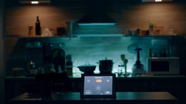 Aplicativo inteligente em tablet colocado na mesa da cozinha em sistema de automação de casa vazia ligando o l ...