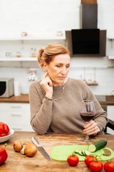 Apoiado na mesa. mulher pensativa de cabelos claros preparando um jantar leve com vegetais enquanto bebe vinho