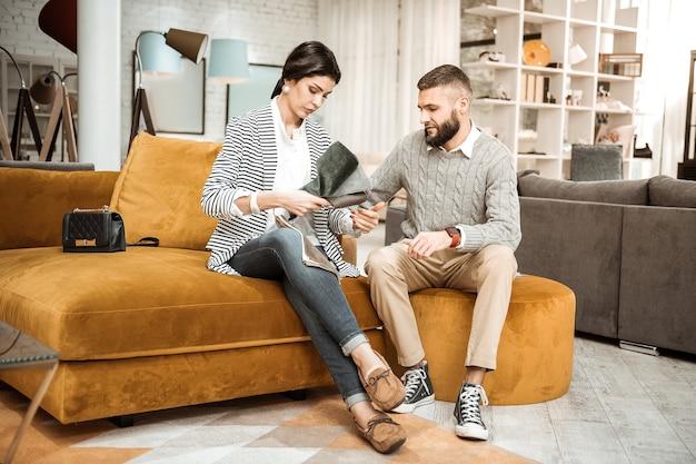 Apoiado na mobília. mulher resoluta de cabelos escuros observando pedaços de material enquanto mostra variantes aceitáveis ao marido