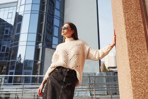 Apoiado na parede com a mão. linda jovem com roupas quentes passeava pela cidade nos fins de semana