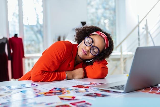 Apoiado nas mãos. senhora incomum exausta com óculos volumosos circulados dormindo no local de trabalho no meio do dia