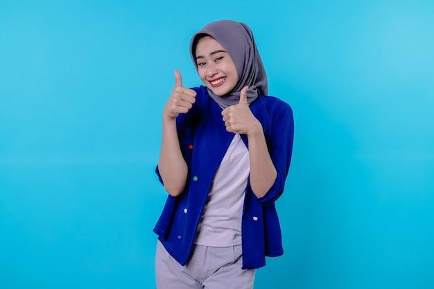 Apoiadora e otimista feliz linda mulher asiática usando hijab com os polegares para cima, impressionada e encantada