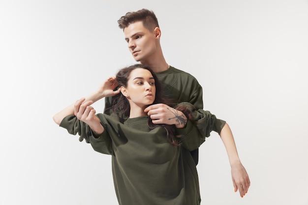 Apoiando. casal na moda elegante isolado na parede branca do estúdio.