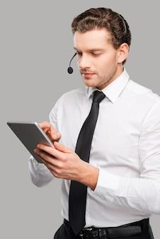 Apoiando o seu negócio. jovem bonito em trajes formais e fone de ouvido, trabalhando em um tablet digital, em pé contra um fundo cinza