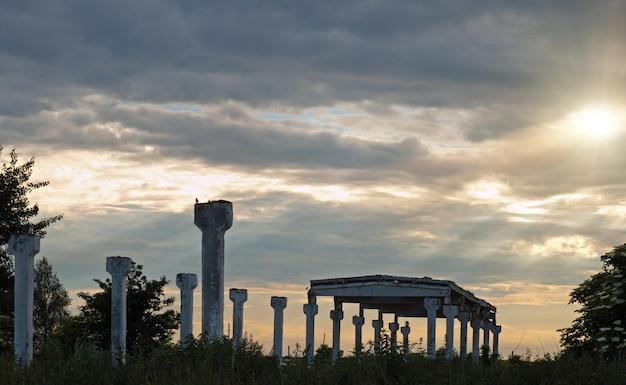 Apoios de construção de fazenda destruída no céu nublado do crepúsculo