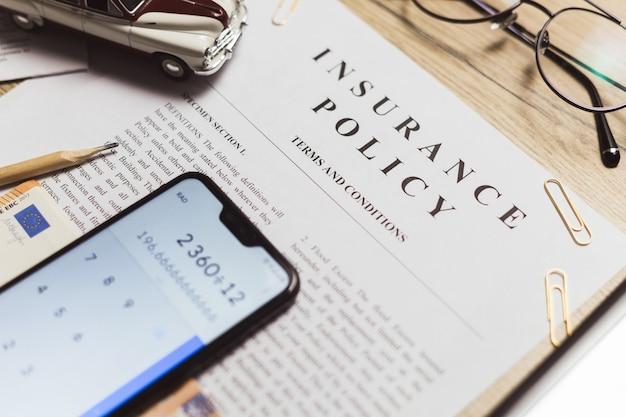 Apólice de seguro de veículos. smartphone com quantia calculada, brinquedo carro retro e dinheiro