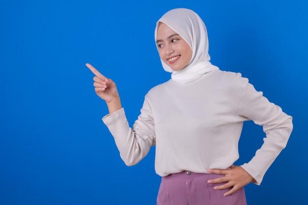Apontando algo jovem e bela muçulmana usando uma camiseta branca