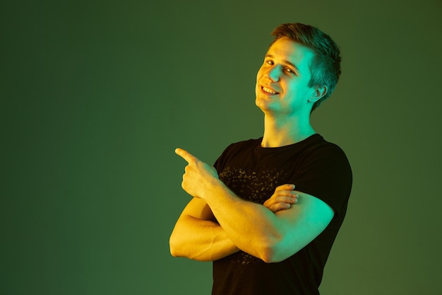 Apontando com as mãos cruzadas. retrato do homem caucasiano isolado no fundo verde do estúdio em luz de néon. lindo modelo masculino de camisa preta. conceito de emoções humanas, expressão facial, vendas, anúncio.