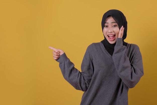 Apontando e surpreendendo algo linda mulher usando camiseta cinza