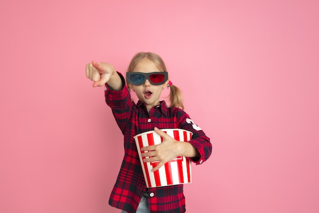 Apontando em óculos 3d. retrato da menina caucasiana na parede rosa do estúdio.