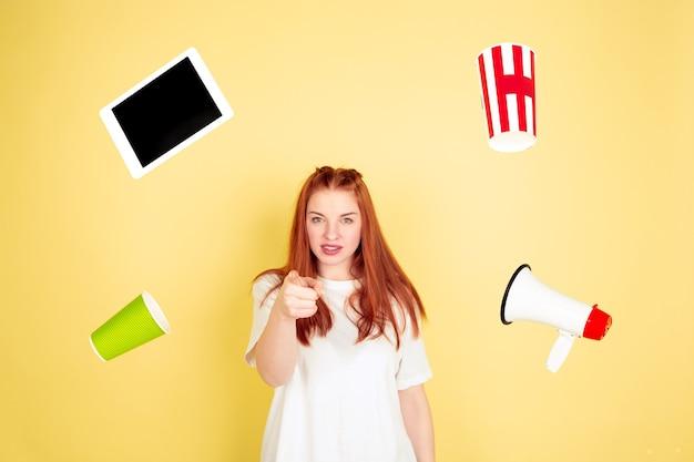 Apontando, escolhendo. retrato de mulher jovem caucasiana em estúdio amarelo