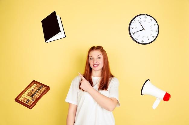 Apontando, escolhendo. retrato de mulher jovem caucasiana em fundo amarelo do estúdio, muitas tarefas. como gerenciar o tempo certo. conceito de trabalho, negócios, finanças, freelance, autogestão, planejamento.