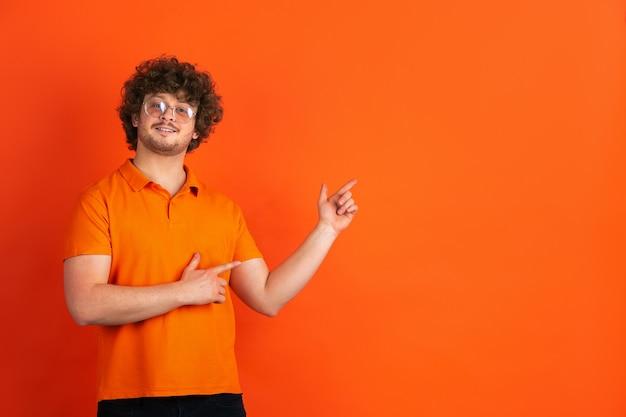 Apontando, escolhendo. retrato monocromático de jovem caucasiano na parede laranja. lindo modelo masculino encaracolado em estilo casual. conceito de emoções humanas, expressão facial, vendas, anúncio.
