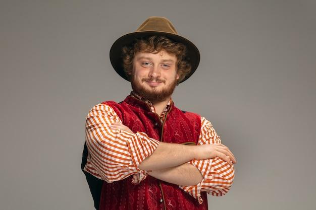 Apontando. homem feliz e sorridente, vestido com o traje tradicional austríaco ou bávaro, gesticulando isolado no estúdio cinza