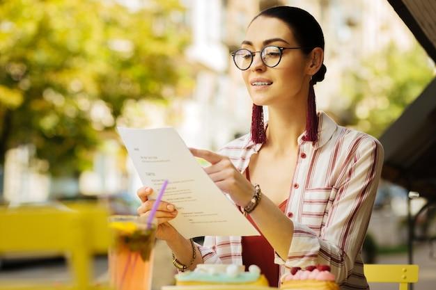 Apontando. mulher calma e confiante sorrindo e escolhendo as refeições do cardápio