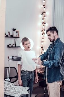 Apontando na página. mestre da tatuagem feminina com corte de cabelo de menino olhando atentamente para a foto da futura tatuagem de seu cliente