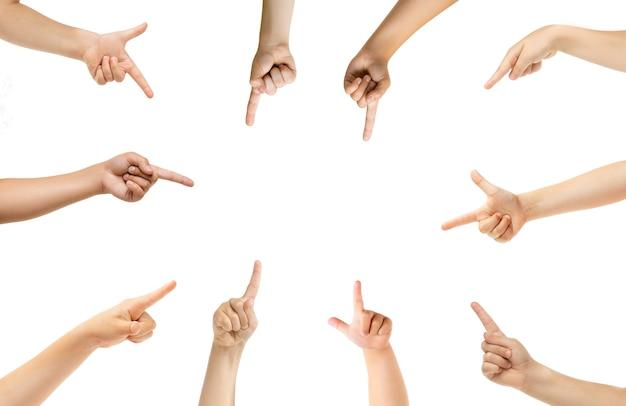Apontando no centro. mãos de crianças gesticulando isoladas no fundo branco do estúdio, copyspace para anúncio. multidão de crianças gesticulando. conceito de infância, educação, pré-escola e tempo escolar. sinais e sentidos.